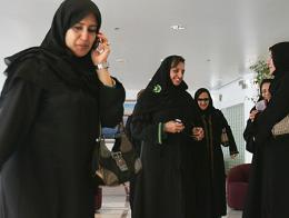 Mujeres saudíes vistiendo la abaya y con la cabeza cubierta por el hiyab, hablando por teléfono