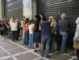 Ciudadanos griegos haciendo cola ante la sucursal cerrada de un banco
