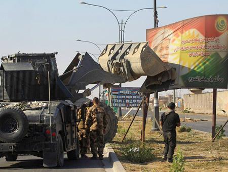 Soldados iraquíes retiran de Kirkuk un cartel con el rostro del líder del KRG, Masud Barzani