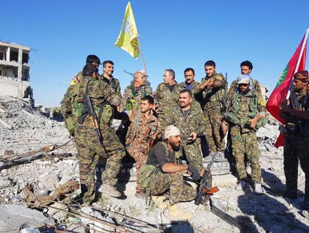 Miembros del SDF entre las ruinas de Raqqa ondeando una bandera de la coalición y otra del YJE, una de las organizaciones adscritas al PKK