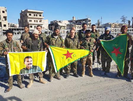 Miembros del YPG muestran banderas del grupo y de Öcalan, líder del PKK, tras la toma de Raqqa