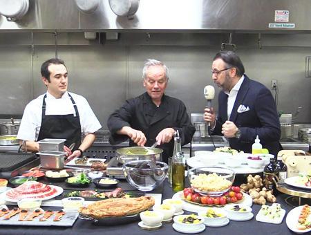 Yiğit Mirzaoğlu junto al chef Wolfgang Puck (centro), entrevistado por un periodista turco